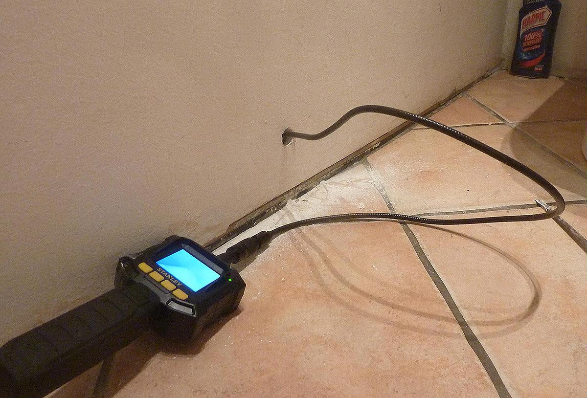 Une petite camera d'inspection pour rechercher des fuites sous le bac à douche